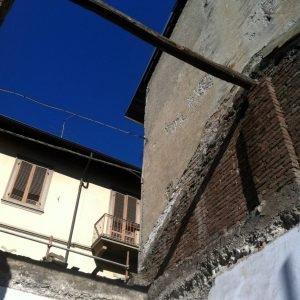 PRIMA DEI LAVORI: Foto della fase di rimozione di tetto e plafoni voltati. L'edificio scoperchiato lasciavedere il cielo e le case circostanti.