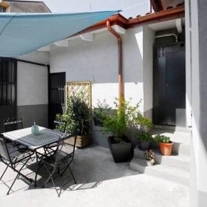 CORTILE INTERNO – Nel cortile interno è stata organizzata un'area ombreggiata per pranzare all'aria aperta. L'ombreggiatura è affidata ad una vela triangolare (Viridea). Tavole e sedie sono in ferro battuto e mosaico.