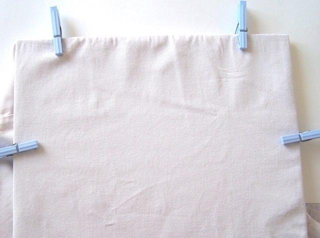 Prendete il cartone e fissatelo sotto la stoffa con l'aiuto delle mollette.