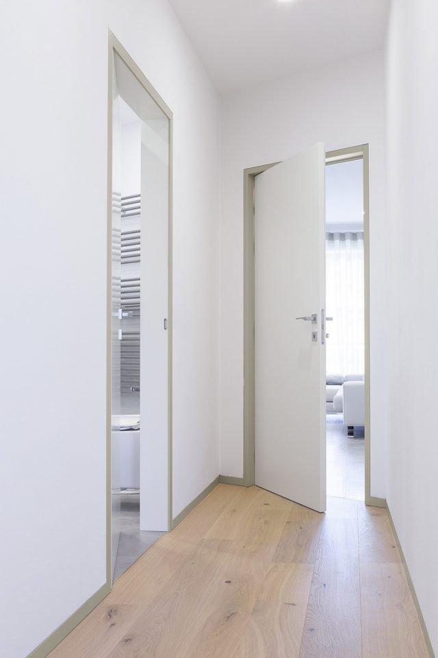 In questa ristrutturazione di una palazzina anni 80 si è optato per porte bianche con coprifili grigio caldo coordinati allo zoccolino, utilizzando i controtelai della linea ECLISSE SHODO Collection.