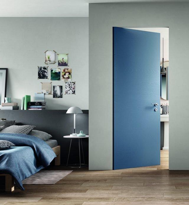 """Porta Equa Zero della linea Sistema Zero di FerreroLegno, nella finitura Trame RAL 5014 Blu Colomba, con telaio """"A_filo"""" completamente integrato nel muro. Dimensioni: 80x210 cm."""