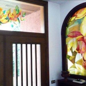 Sopraporta in vetro e specchiera dipinti con motivi floreali.