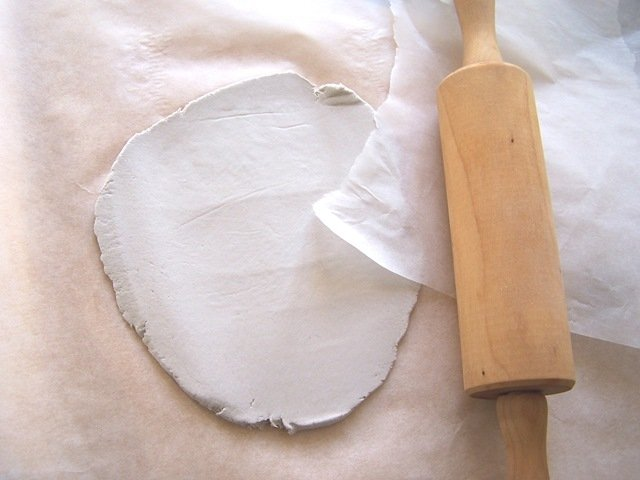 Prendete la pasta modellabile e mettetela tra due fogli di carta da forno. Spianatela con un matterello fino a creare uno strato di circa mezzo centimetro.