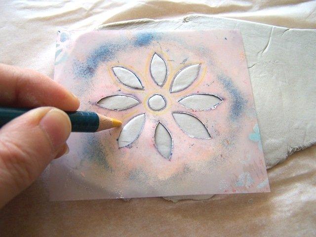 Prendete lo stencil e poggiatelo sul pasta da modellare. Con una matita ripassare i bordi dello stencil, per far fuoriuscire la pasta dai fori e rendere il decoro più in rilievo.