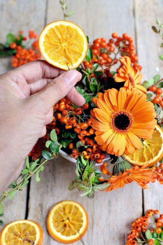 6. Disponete sull'asse arancione le tazze floreali, alternandole alle arance con tealight e alle candele di varie misure.