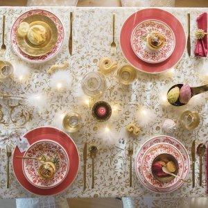 Fiabesca la tavola di Natale di Coincasa dominata dalla tovaglia stampata con eleganti fiori dorati (misura L 140 x  P 240 cm, prezzo 39,90 euro) rallegrata dai tovaglioli rossi con il bordo in pizzo (prezzo 8,90 il set di 2 pezzi). I piatti con il decoro floreale Adelasia nei toni del rosso sono in ceramica realizzata e dipinta a mano in Sicilia (prezzo a partire da 14,90 euro cad.), i bicchieri in vetro trasparente hanno la base foglia oro che dà vita a suggestivi riflessi (prezzo 4,90 euro cad.). Le posate color oro (prezzo 169,90 euro il set di 24 pezzi) e il piatto ovale in vetro con decoro bisanzio (prezzo 39,90 euro) completano la composizione. Il tocco finale:  la catena Piuma con sedici luci a Led che si snoda sull'intera tavola (prezzo 14,90 euro)! www.coin.it