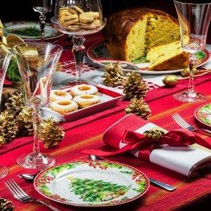 Stile New England per la tavola di Natale con i piatti del servizio Rosso Natale di Henriette: sono tutti realizzati in candida porcellana e al centro raffigurano i classici simboli delle feste come Babbo Natale, l'abete addobbato, il vischio, gli angeli... Il bordo è  decorato da una ghirlanda di bacche rosse. Si possono accostare al centrotavola, alle coppette, alla teiera e ai mug coordinati. Il set di 4 piatti dessert, prezzo 56 euro. Il piatto torta con paletta, misura ø 31 cm, prezzo 49 euro. www.henriette.sm