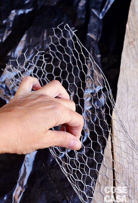 1. Tagliate il telo di plastica nero (potete utilizzare il sacchetto del terriccio, girandolo al rovescio) di 80 cm di lunghezza e 30 cm di larghezza. Dalla rete di metallo, invece, tagliate una striscia lunga 80 centimetri e larga circa 25 cm, poi modellatela curvandone i bordi nella larghezza.