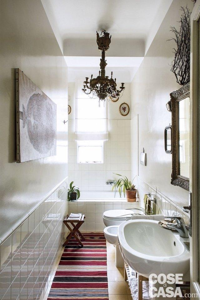 bagno con lampadario chandelier, lavabo, sanitari e vasca nel sottofinestra