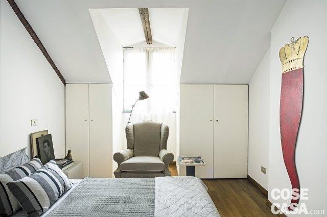 camera in mansarda con finestra a cappuccina e armadi nel sottotetto