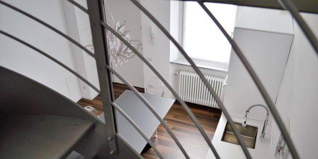 Una mansarda con scala elicoidale e pavimento in piastrelle effetto legno