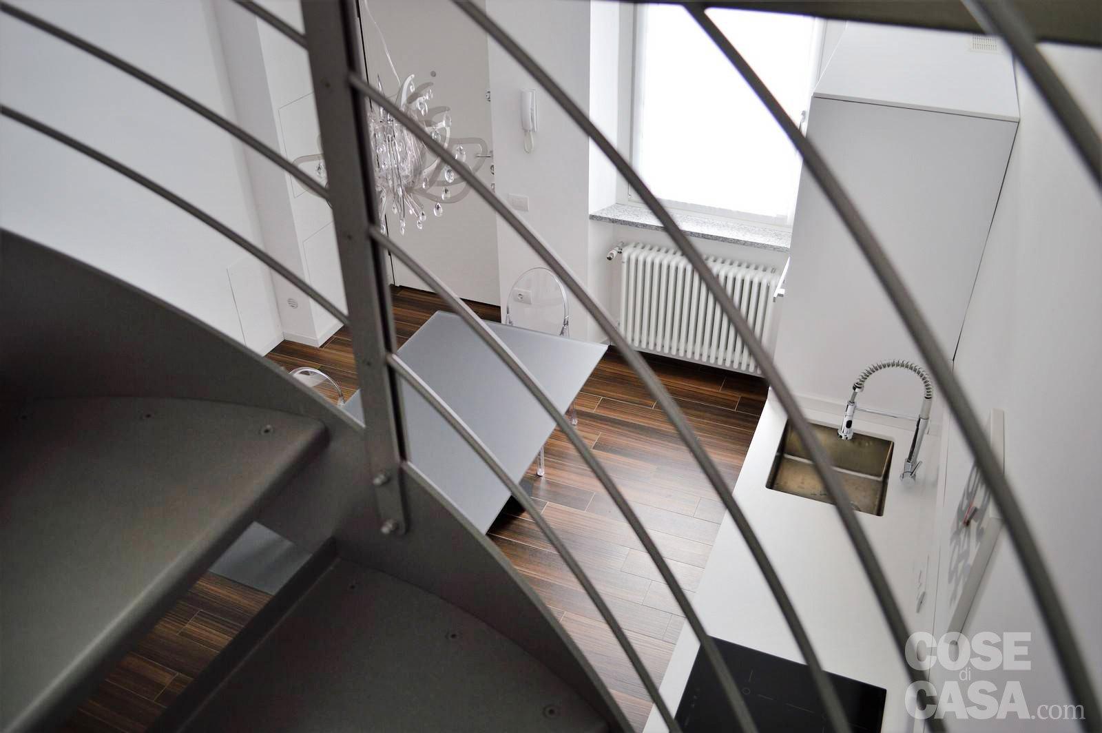 Una mansarda con scala elicoidale e pavimento in piastrelle
