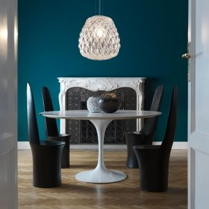 Parete blu intenso, nella zona pranzo con lampadario di FontanaArte. www.fontanaarte.com