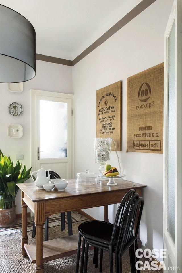 in cucina, tavolo con sedie impilate e dispensa con porta vetrata