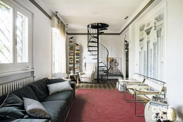 nel sottotetto d'epoca divano e poltrone di design, con scala a chiocciola
