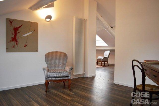 Una mansarda con scala elicoidale e pavimento in for Studio arredato