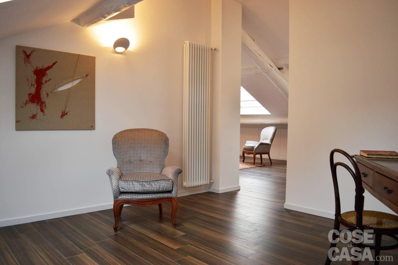 Una mansarda con scala elicoidale e pavimento in piastrelle effetto