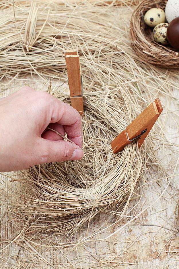 1. Cominciamo con la realizzazone del nido utilizzando della paglia morbida o, meglio ancora, il materiale di risulta della potatura delle graminacee che va effettuata generalmente a fine inverno. Attorcigliate i fusti secchi della graminacea tra loro e legateli con la corda sottile. Poi arrotolateli legando insieme due o più giri di fasci di fusti e fermateli con alcune mollette da bucato.