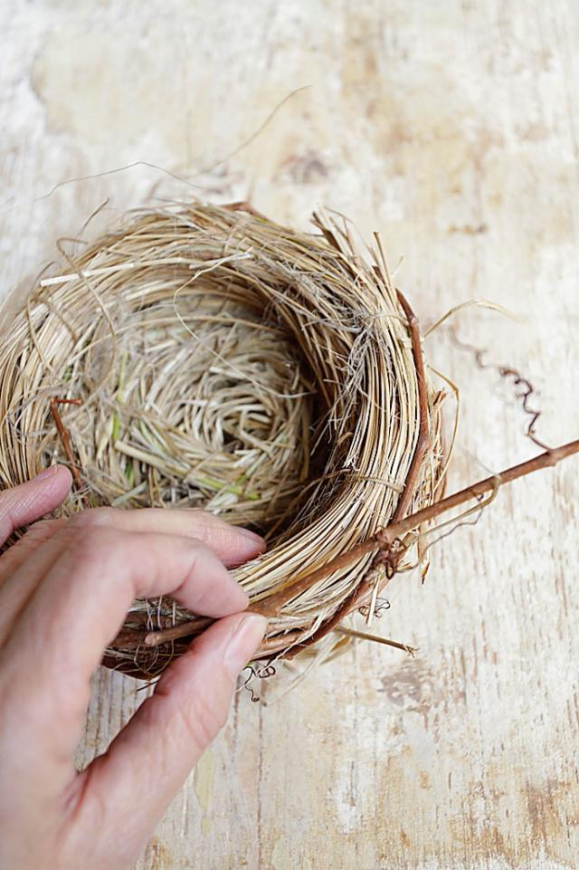 2. Per fissare facilmente il nido alla ghirlanda di Pasqua, attorcigliate subito attorno al nido un tralcio del rampicante che servirà per fare la ghirlanda.
