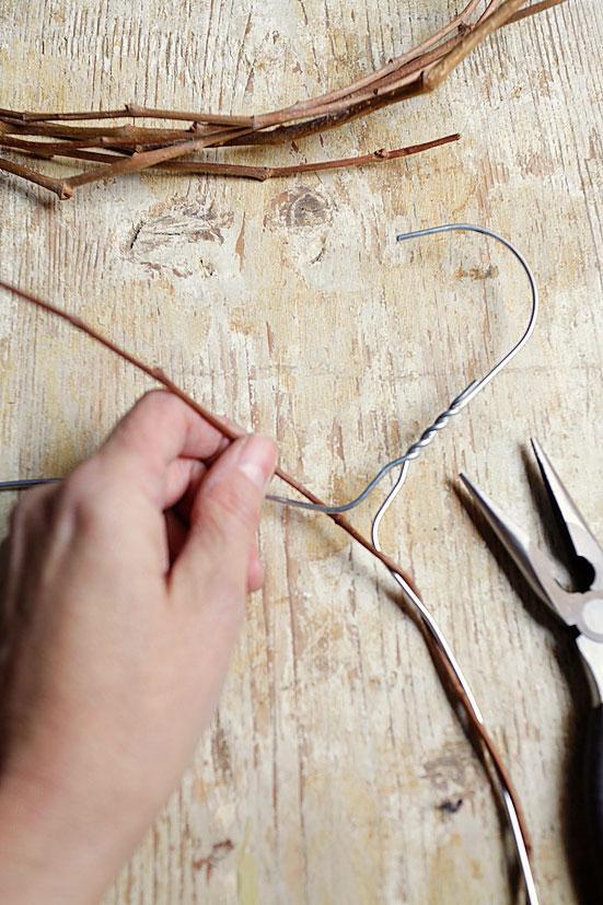 4. Per fare la ghirlanda di Pasqua, procuratevi una gruccia in metallo da tintoria, quelle semplici in filo di ferro: è un'ottima base per fare diverse decorazioni. Con le pinze modellate la gruccia a forma di ovale. Poi, armati di pazienza, procedete avvolgendo i tralci lunghi e flessibili, senza spine, sulla base di ferro della gruccia, uno dopo l'altro, a spirale, seguendo lo stesso senso di intreccio. Per creare una certa consistenza occorre avvolgere molti tralci.