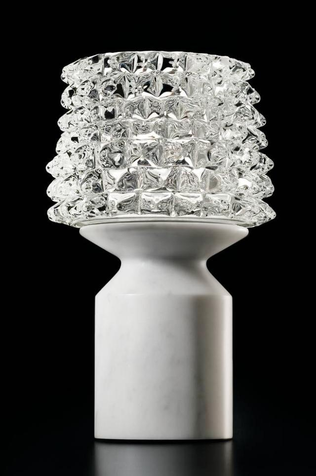 Camparino di Barovier & Toso, è la lampada da tavolo ispirata agli Anni Trenta: è realizzata con la tecnica muranese del rostrato, una complessa lavorazione artigianale del vetro inventata nel 1938, che dà vita ad una serie di punte sul paralume; la base è in marmo pregiato. É alimentata da una batteria al litio ricaricabile  che permette di trasportare la lampada dove si desidera; inoltre la tecnologia contactless consente l'accensione, lo spegimento e la regolazione dell'intensità luminosa. www.barovier.com