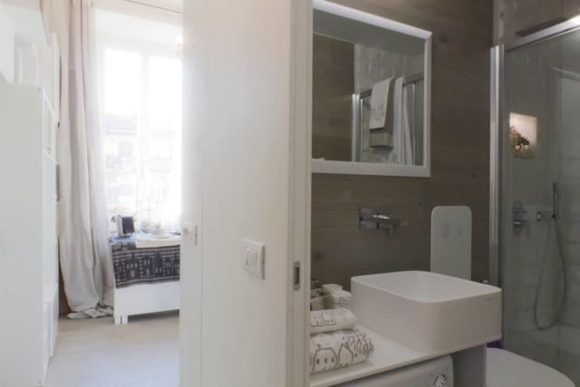 (foto8) Il bagno, posizionato all'ingresso della casa per potenziarne la superficie e lasciare piena visuale alla finestra, sfrutta come rivestimento verticale le medesime plance del parquet. Il disegno su misura degli arredi e un grande specchio ne potenziano lo sfruttamento funzionale oltre che la percezione ottica e la luminosità.