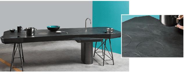"""Le zone cottura a induzione sono mimetizzate all'interno del top in pietra, liberando la superficie dalla presenza di piastre o bruciatori. Nascosta nel piano c'è anche la ricarica per il cellulare. Anche il rubinetto e la cappa si azionano con comandi touch. La bilancia touch screen, retroilluminata a led, fa tutt'uno con il piano di lavoro, rimanendo invisibile. È un prototipo la cucina a isola polifunzionale Tulér, sviluppata all'interno di Offmat, laboratorio di ricerca di Marmo Arredo (www.marmoarredo.com). Il top in quarzo tecnico nasconde una tecnologia """"responsive"""", in grado, cioè, di rispondere ai comandi impartiti."""