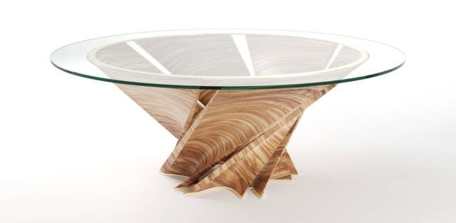 Torsion Table di Natuzzi Italia, design Mario Bellini, è il tavolo  rotondo imponente e scenografico, formato dalla base composta da sei petali in massello di ulivo che si intrecciano sormontata da un piano in vetro extrachiaro. Le dimesnioni e la forma lo rendono simile ad una scultura contemporanea. www.natuzzi.it