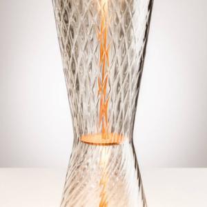 Tiara Lampade di Venini, design Francesco Lucchese, è la lampada da tavolo realizzata in vetro di Murano. Il diffusore, in vetro soffiato e lavorato a mano, ha una texture tridimensionale che crea effetti luminosi sorprendenti ed è impreziosito dai dettagli metallici; la sorgente luminosa è a Led. Misura ø 19 x H 46 cm. www.venini.com