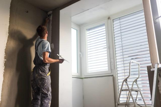 Plasterer renovating indoor walls and ceilings. Construction finishing works.