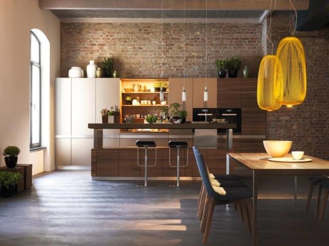 """K7 di Team7 è la cucina con uno stile urban caratterizzata dall'isola centrale con il piano, regolabile in altezza, realizzato  in agglomerato di quarzo colore snow desert, un materiale che garantisceuna superficie da lavoro igienicamente perfetta, di lunga durata e resistente a graffi, macchie e alte temperature. Le ante sono in noce e in vetro colore acciaio. Prezzo su richiesta. w HYPERLINK """"http://Www.team7.it/""""ww.team7.it"""