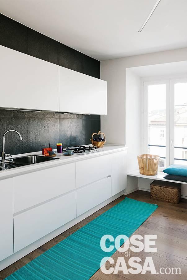 Cucina in linea, laccato bianco lucido, rivestimento in gres con texture in rilievo