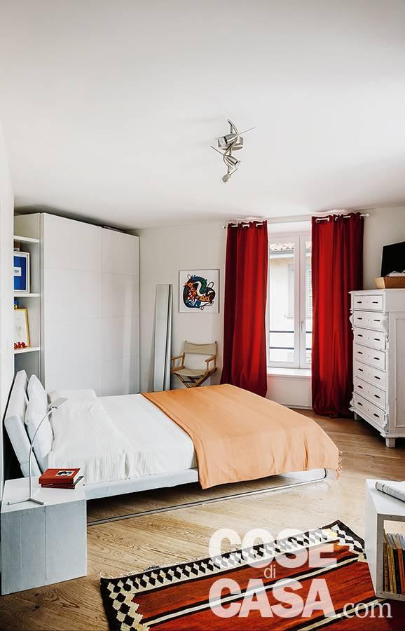 camera matrimoniale, letto tessile, armadio, settimanale bianco, tende e tappeto rossi