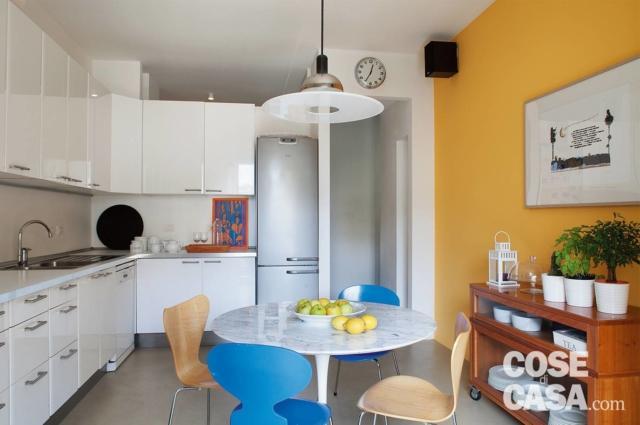cucina, parete arancio e tavolo rotondo