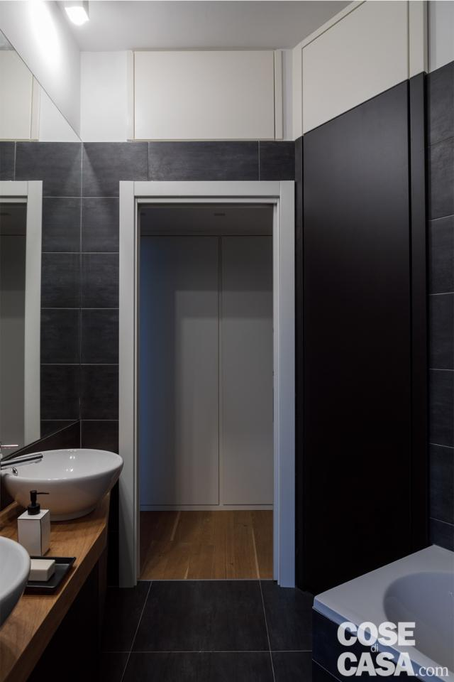 porta del bagno con ripostiglio in quota nella casa con soggiorno open space