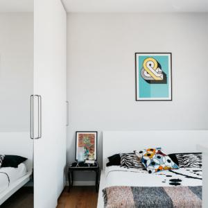 Nella camera matrimoniale, l'armadio a tutta altezza con ante in laccato bianco e specchiate e il letto sono stati su misura. Al centro del soffitto, le pale del ventilatore.