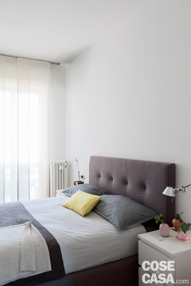 camera e letto tessile con testiera capitonné nell casa con soggiorno open space