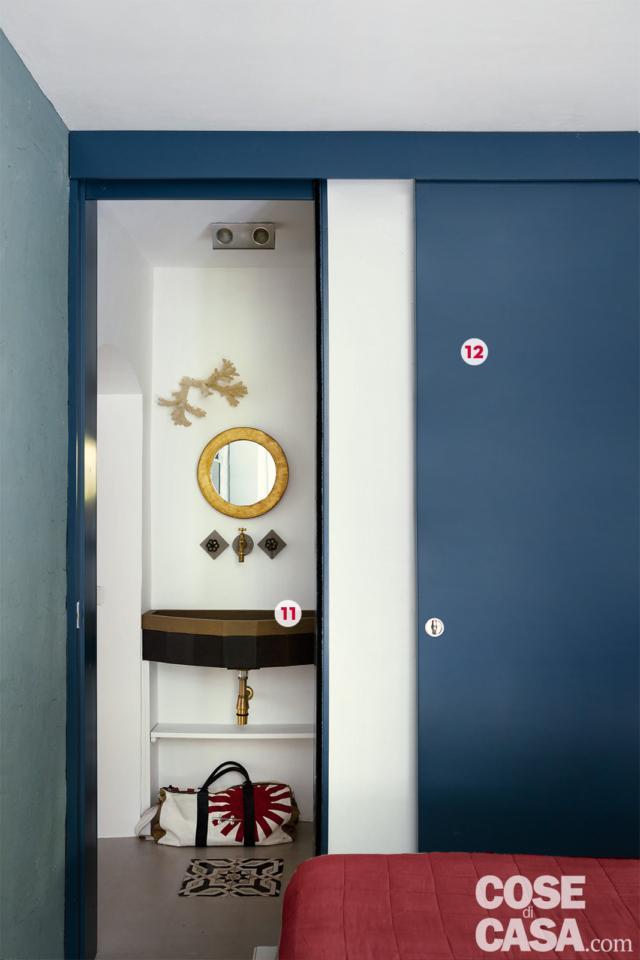camera pannello scorrevole e lavabo sospeso con specchio dorato in abitazione ex legnaia soggetta a recupero