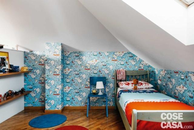 Nella cameretta azzurra del bambino, posata nella zona intorno al letto, la carta da parati riproduce un planisfero stilizzato