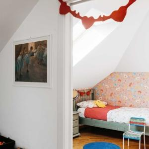 Nella cameretta rosa della bambina, nel sottotetto rinnovato, la tappezzeria definisce e incornicia la parete che fa da sfondo al letto