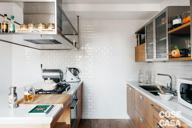"""Il soffitto della cucina forma un """"gradino"""" per passaggio degli impianti. La cappa in acciaio spazzolato è integrata in una struttura sospesa, sempre in acciaio."""
