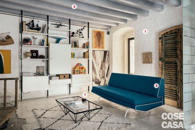 in soggiorno, divano trasformabile vintage e libreria a parete