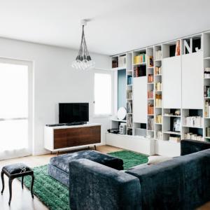 Soluzioni per contenere su disegno risolvono due intere pareti. I serramenti della finestra e della portafinestra sono quelli originali in legno laccato bianco.