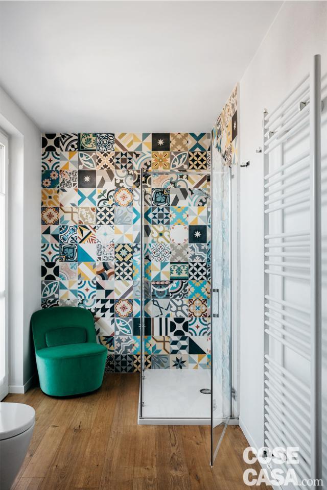 """Nel bagno del sottotetto rinnovato i decori policromi delle cementine a parete, la luminosità naturale e dettagli quali la poltroncina """"da salotto"""" nell'angolo."""