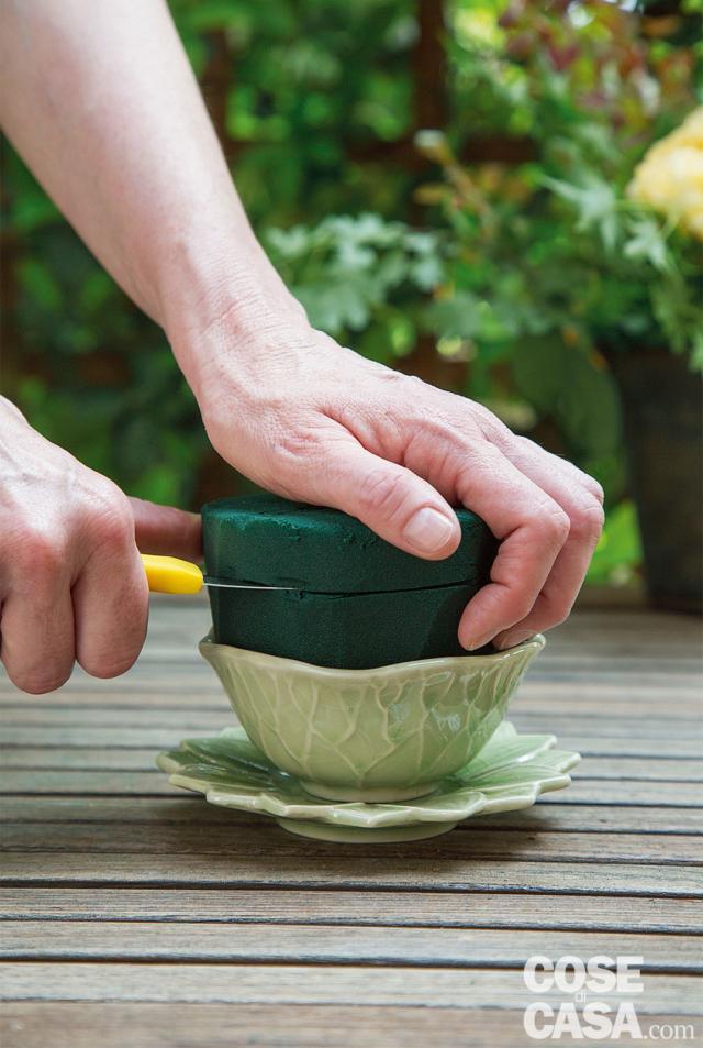 2. Inserire la spugna tagliata nella tazza e abbassarne l'altezza fino a 2 cm sopra il bordo, quindi smussare i lati per avere una maggiore superficie in cui inserire i fiori.