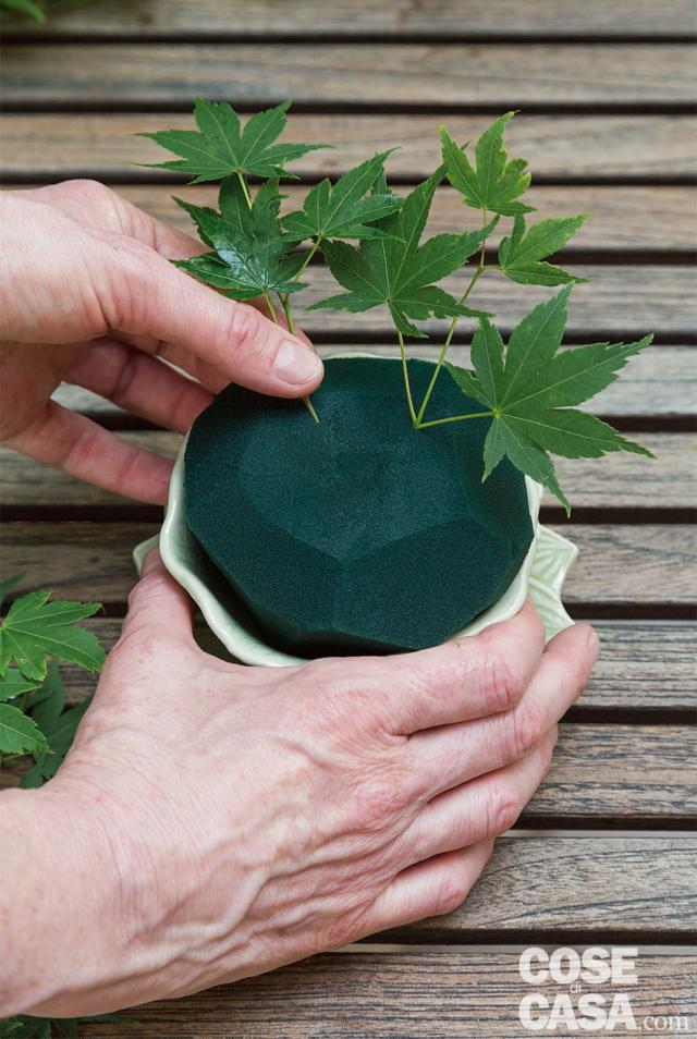 3. Creare una base verde inserendo le cime terminali dei rametti di Acer palmatum, tenendo sempre un'inclinazione obliqua. Lasciare spazio anche per gli altri elementi.