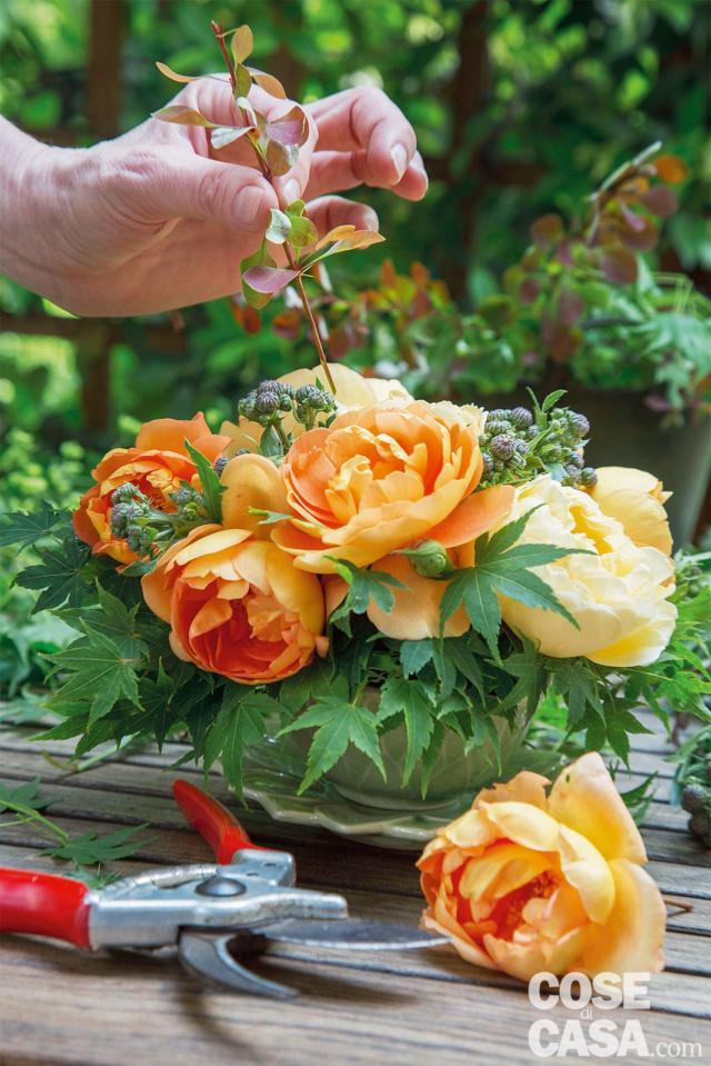 Per ultimare il lavoro dei fiori in tazza, inserire i rametti di Berberis, lasciandoli sporgere dalla composizione per sottolineare le note calde e ambrate dei fiori principali, in contrasto con quelle fresche dei fiori di complemento e delle foglie. Serve anche per movimentare ulteriormente la composizione.