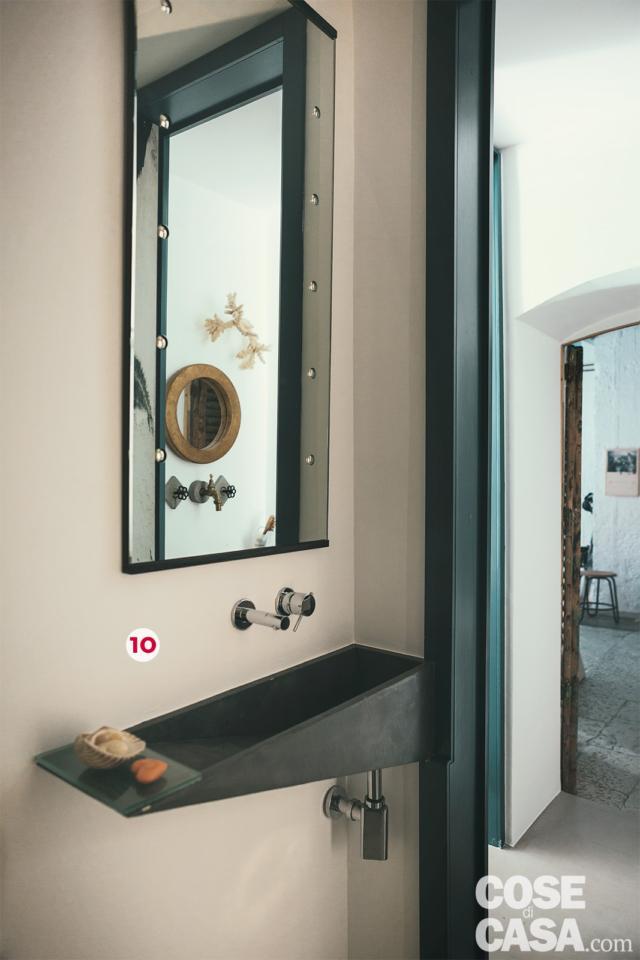 lavabo in pietra nera con rubinetteria a parete in abitazione ex legnaia soggetta a recupero