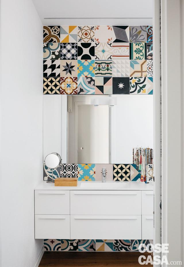 Nella zona lavabo il rivestimento policromo incornicia, sopra e sotto, il volume sospeso del mobile in laccato bianco opaco e la specchiera senza cornice.