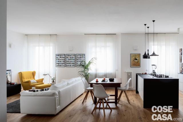 soggiorno open space con divano, tavolo e cucina a vista